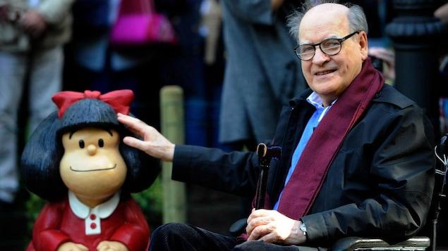 Quino, en fauteuil roulant, pose à côté de Mafalda.