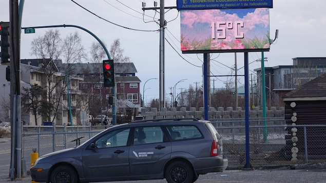 On voit un panneau d'affichage où est indiqué 15 degrés Celsius et une voiture stationnée.