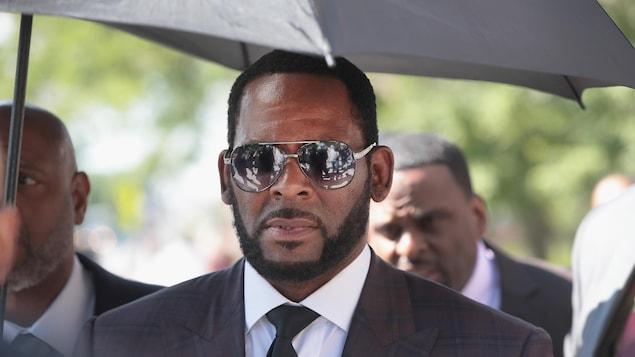 Le chanteur R. Kelly portant un complet et des verres fumés.