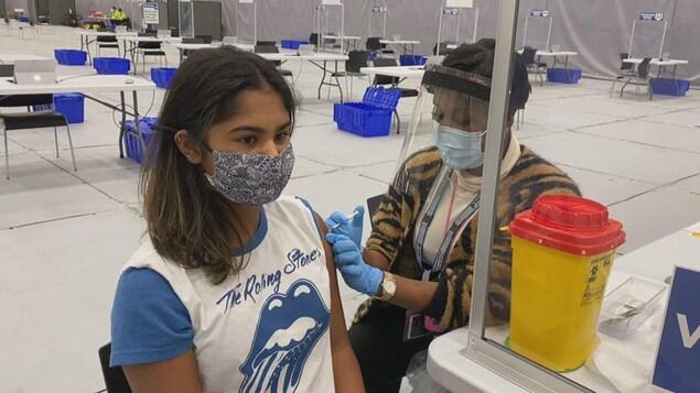 Une jeune fille masquée reçoit un vaccin