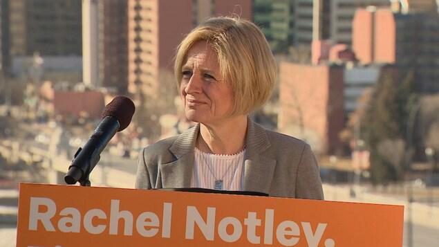 Gros plan sur une femme blonde qui se trouve dehors devant un micro avec en arrière plan le centre-ville.