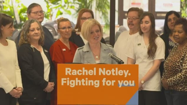 Une femme blonde fait un discours derrière un pupitre où il est écrit en anglais: « Rachel Notley. Fighting for you ». Un groupe de personnes se trouvent derrière elle.