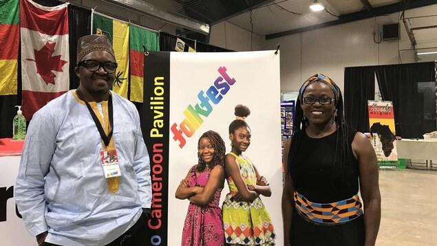 Les deux ambassadeurs posent fièrement à côté de l'affiche du FolkFest de Saskatoon.