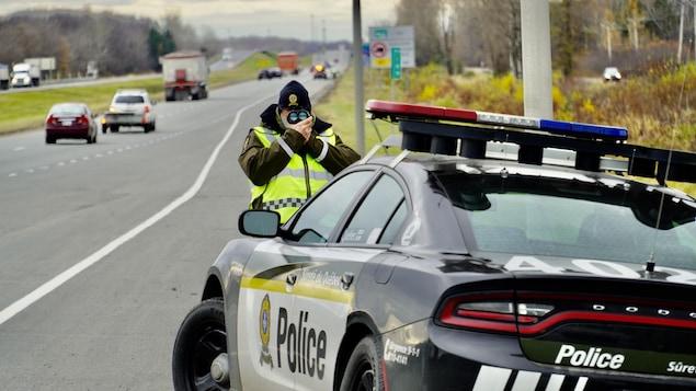 Un policier sur le bord de l'autoroute tient un radar.
