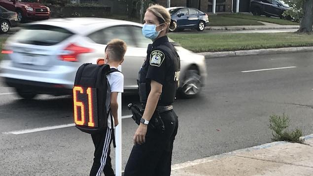 Un enfant porte on sac à dos sur lequel la vitesse de 61 km/h est affichée, sous le regard attentif d'une policière de Laval.