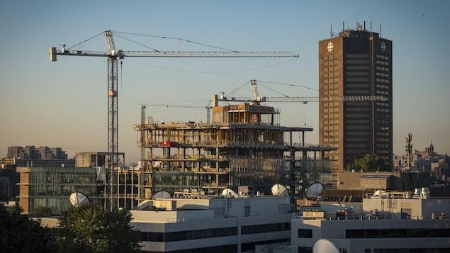 Des grues construisant un immeuble au centre-ville de Montréal.