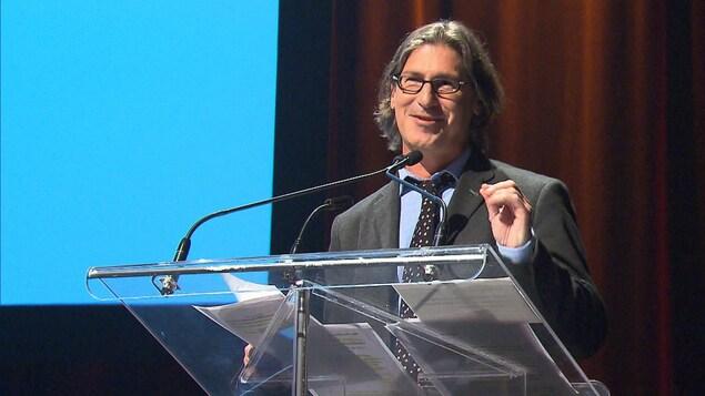 Jean-René Dufort parle derrière un lutrin.