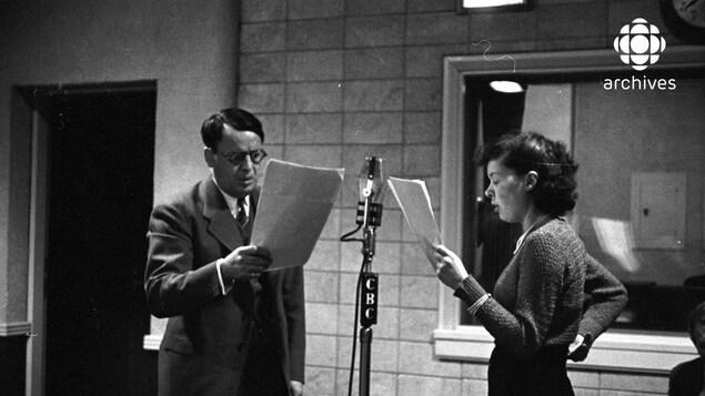 Dans un studio de radio, le comédien Albert Duquesne interprétant le rôle d'Alexis Labranche, et la comédienne Estelle Maufette interprétant le rôle de Donalda, lisant leur texte derrière un micro.