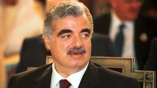 Rafic Hariri assis sur une chaise tourne la tête pour regarder à gauche.