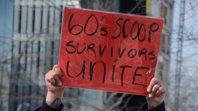 Une personne brandit une pancarte.