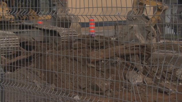 Des morceaux de bois et de pierre faisant autrefois partie d'un système de tramway au pied d'une pelle mécanique.