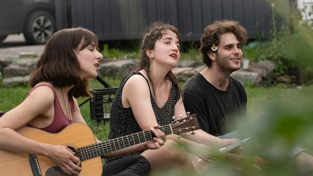Trois personnes chantent et jouent de la guitare assises dans le gazon.