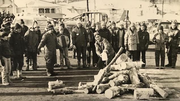 Manifestants devant un monticule de bois sur la route.