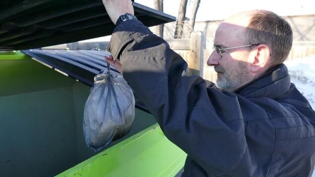 Alan Forbes, de la branche Manitoba de l'Institut canadien des condominiums, jette un sac d'ordures dans un grand bac à l'extérieur.