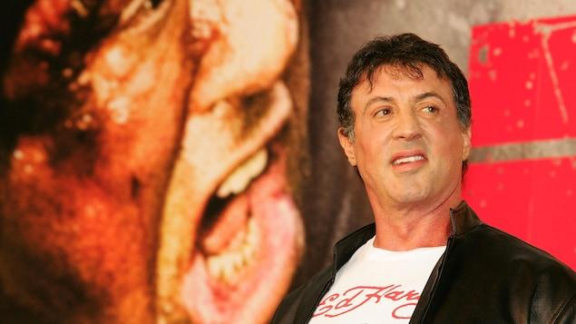 L'acteur Sylvester Stallone pose devant une affiche du film Rambo.