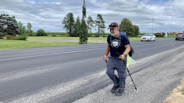 Un homme marche sur le bord de la route.