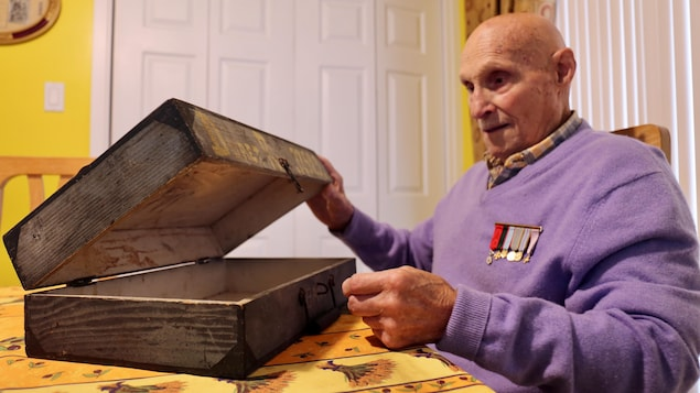 Un homme avec des médailles militaires regarde une boîte en bois