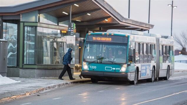 Un homme monte à bord d'un autobus.
