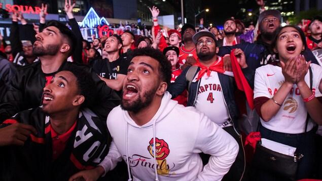 Des partisans torontois réunis à l'extérieur la nuit réagissent à la victoire des Raptors.