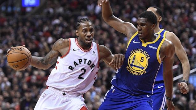Photo d'un homme avec le ballon qui pousse un autre joueur avec le bras.