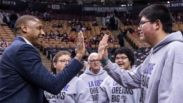 Le président des Raptors de Toronto tape dans la main d'un étudiant de la petite communauté de La Loche.