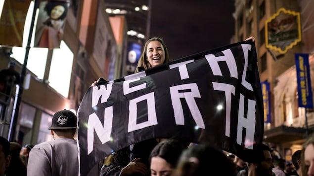 Photo d'une jeune femme qui tient un drapeau noir avec le message «We the North».