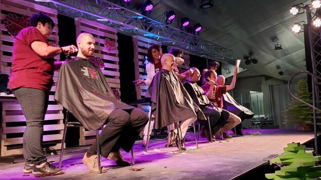 Trois personnes se font raser la tête simultanément sur une scène.