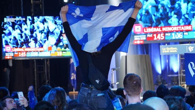 Une partisane agite le drapeau du Québec au rassemblement du Bloc.