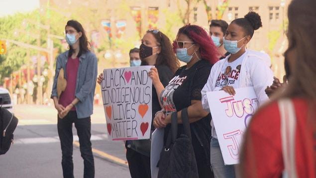 Des manifestants brandissent des affiches.