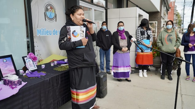 Une femme au micro devant le centre d'amitié autochtone; une table avec une photo de Joyce Echaquan et des gens sur le trottoir qui écoutent.