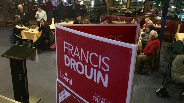 Une foule rassemblée dans un restaurant avec une pancarte électorale à l'avant-plan.