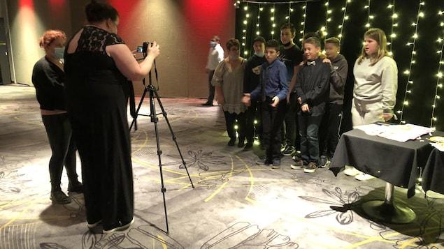 Une femme prend en photo un groupe de jeunes.