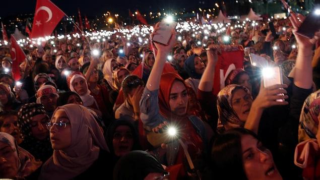 Une foule de personnes brandissant des drapeaux turcs et leur cellulaire avec le flash allumé dans la nuit
