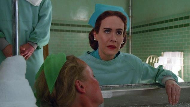 Une infirmière regarde devant elle alors qu'une autre est couchée devant elle.