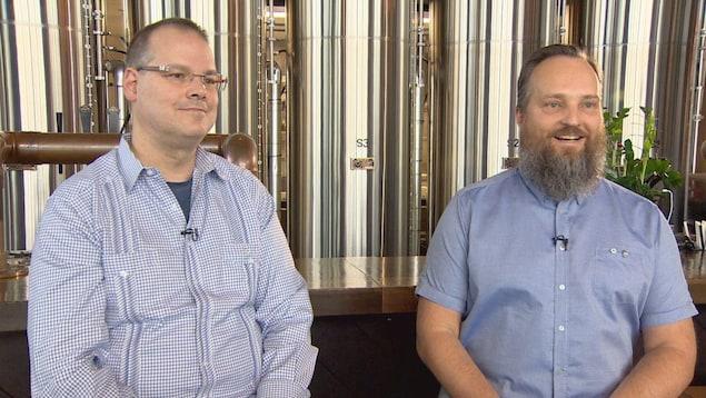 Ray Muzyka et Greg Zeschuk sont assis devant des cuves de bières en inox.