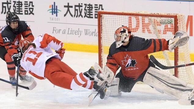 Une gardienne de but canadienne fait un arrêt devant une joueuse russe.