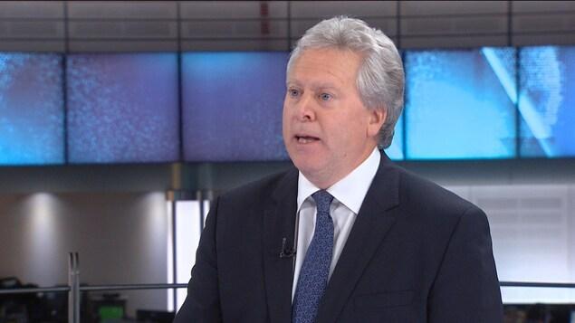 Un homme en veston-cravate se trouve sur un plateau d'émission et a la bouche ouverte, comme s'il parlait.