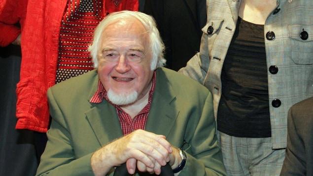 Raymond Lévesque assis, tenant sa canne devant lui.