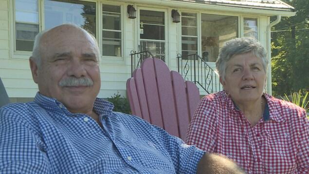 Un homme et une femme sont assis devant leur maison, dans des chaises sur leur perron.