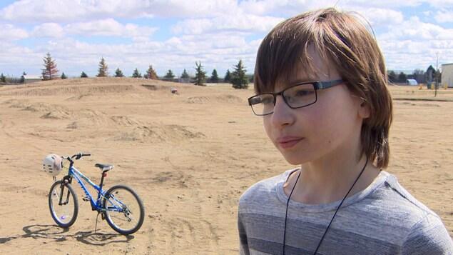 Un jeune garçon au milieu d'un terrain de terre avec des bosses, à côté de son vélo.