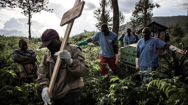 Des infirmiers transportent un cercueil derrière un homme qui tient une croix en bois.