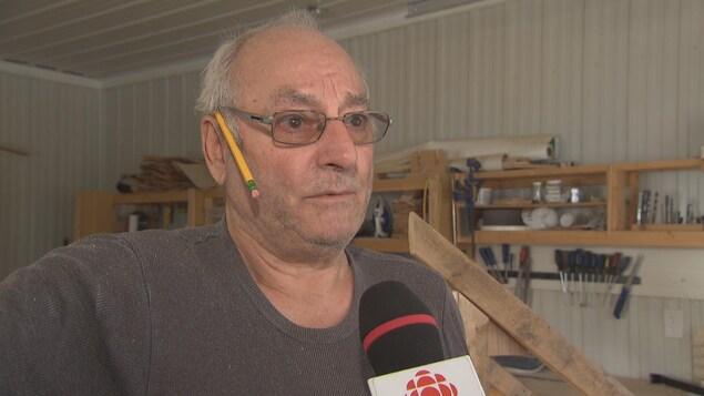 Un homme donne une entrevue à Radio-Canada dans un établi alors que des outils se retrouvent en arrière-plan.