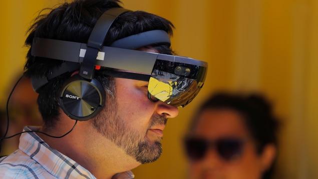 Une photo montrant un homme portant un masque de réalité mixte Hololens, qui ressemble à de grosses lunettes de ski, et un casque d'écoute.