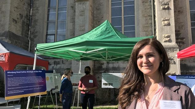 Rebecca Peterniak est debout devant un kiosque d'information de la Ville de Winnipeg. Elle sourit, le visage au soleil.
