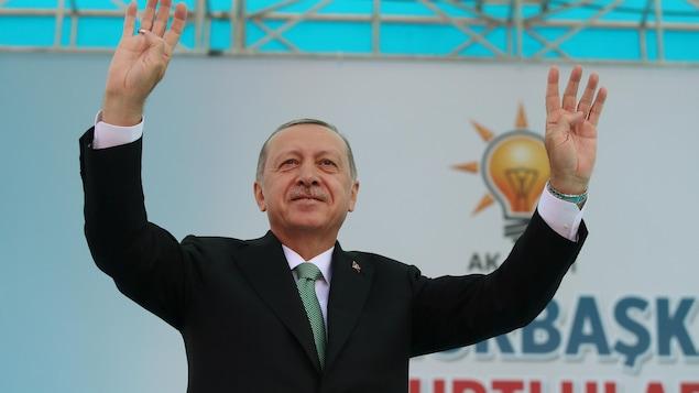 Le président Erdogan, les deux bras dans les airs, sur une scène.