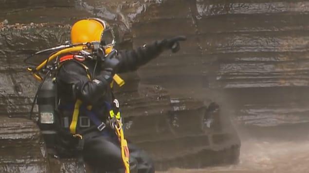 Un scaphandrier s'apprête à plonger dans le bassin au pied des chutes Jean-Larose.
