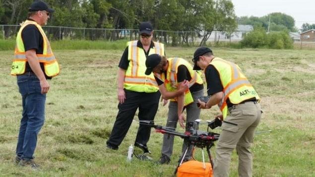 Quatre hommes sont autour d'un drone dans un large espace gazonné.