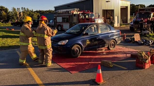 Deux pompiers s'approchent d'un véhicule accidenté