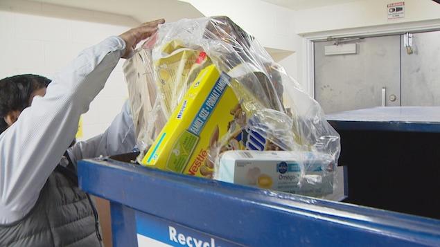 Photo d'un homme qui dépose des boîtes et du papier dans un bac de recyclage.