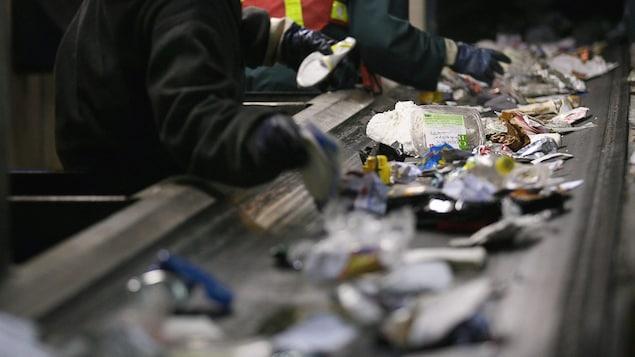 Des employés trient le contenu de bacs de recyclage à une usine.